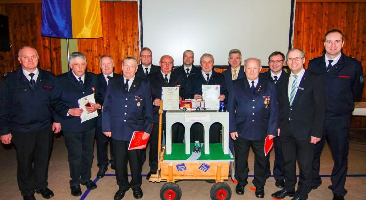 Die Geehrten vor dem Wappenzeichen der Gemeinde: Bürgermeister Hans-Jürgen Wessels (5. von links) und Landrat Manfred Müller (2. von links) zeichnen die verdienten Feuerwehrleuten für ihre Treue aus.